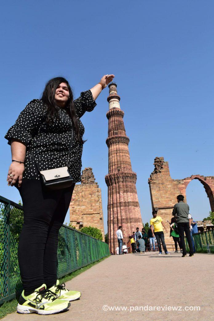 holding qutub minar photo